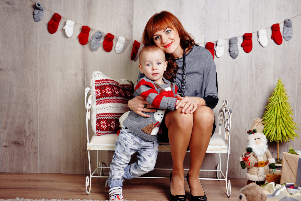Happy mother with a baby sitting and waiting for Christmas. Waiting for baby gifts with his mother sitting on the bed before Christmas. In anticipation of Christmas.